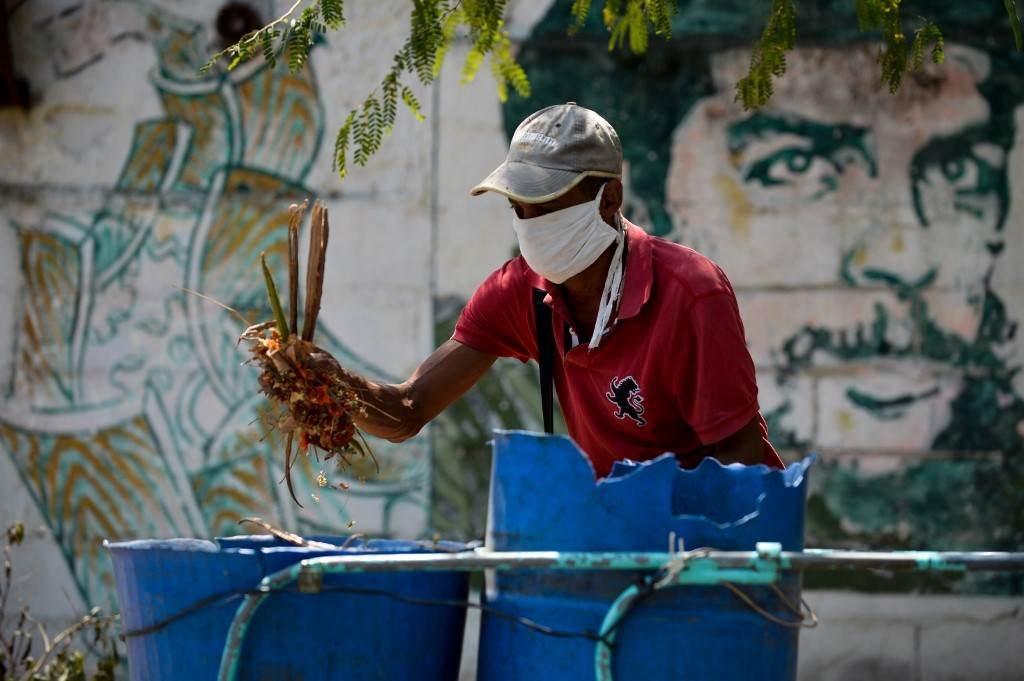 عامل نظافة يرتدي قناعاً واقياً في العاصمة هافانا ويظهر خلفه غرافيتي للمناضل الأممي ارنستو تشي غيفارا (أ.ف.ب)
