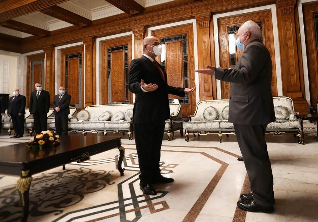 الرئيس العراقي برهم صالح خلال استقباله وزير الخارجية الإيراني محمد جواد ظريف اليوم في بغداد (أ.ف.ب)