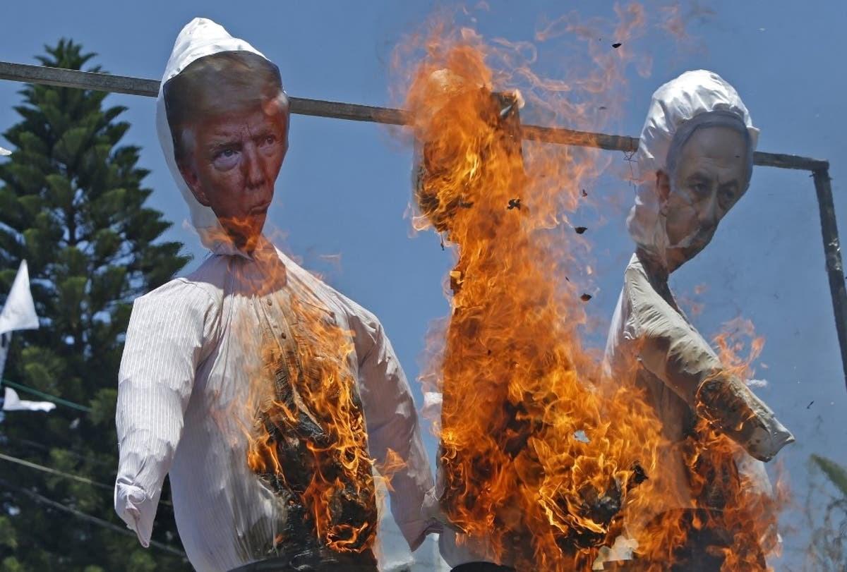 متظاهرون فلسطينيون  ضد صفقة القرن يحرقون دمى لترامب ونتنياهو في قطاع غزة يوم 7 يوليو 2020 (أ.ف.ب)