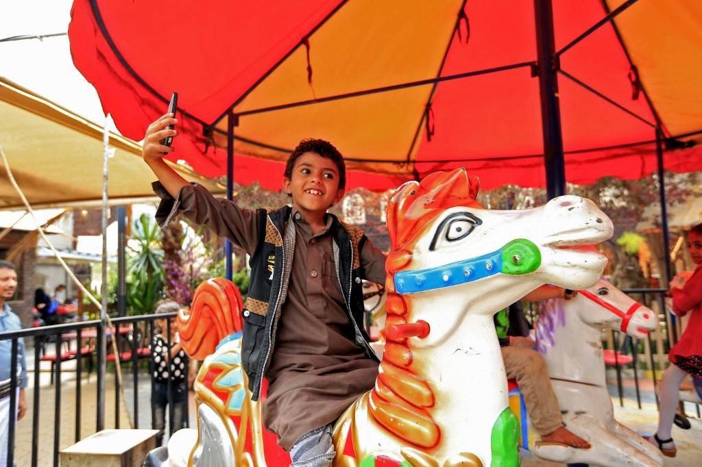 طفل يمني يلتقط صورة سيلفي في مدينة ألعاب في العاصمة صنعاء (أ.ف.ب)