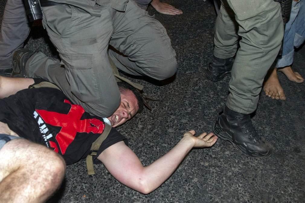 عنصر شرطة إسرائيلي يجثو بركبته على عنق متظاهر في القدس المحتلة (الثلاثاء)
