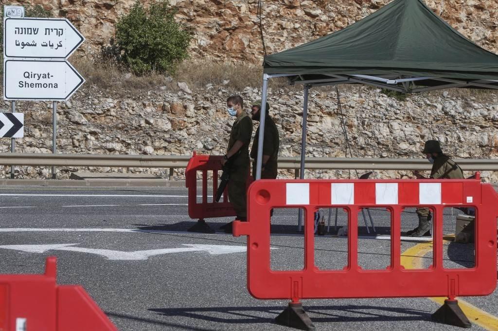 جنود إسرائيليون يديرون نقطة تفتيش على طريق بالقرب من الحدود مع لبنان (أ ف ب).