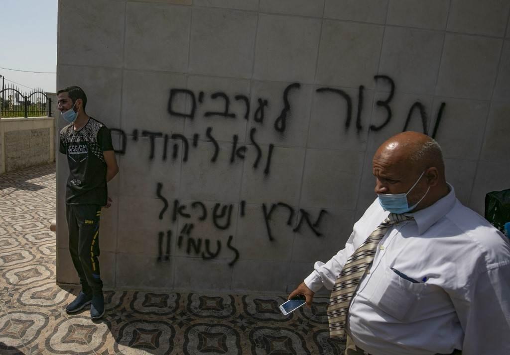 فلسطينيون يتفقدون الأضرار التي لحقت بمسجد البيرة الذي تمّ رشه بالكتابات العبرية (أ ف ب).