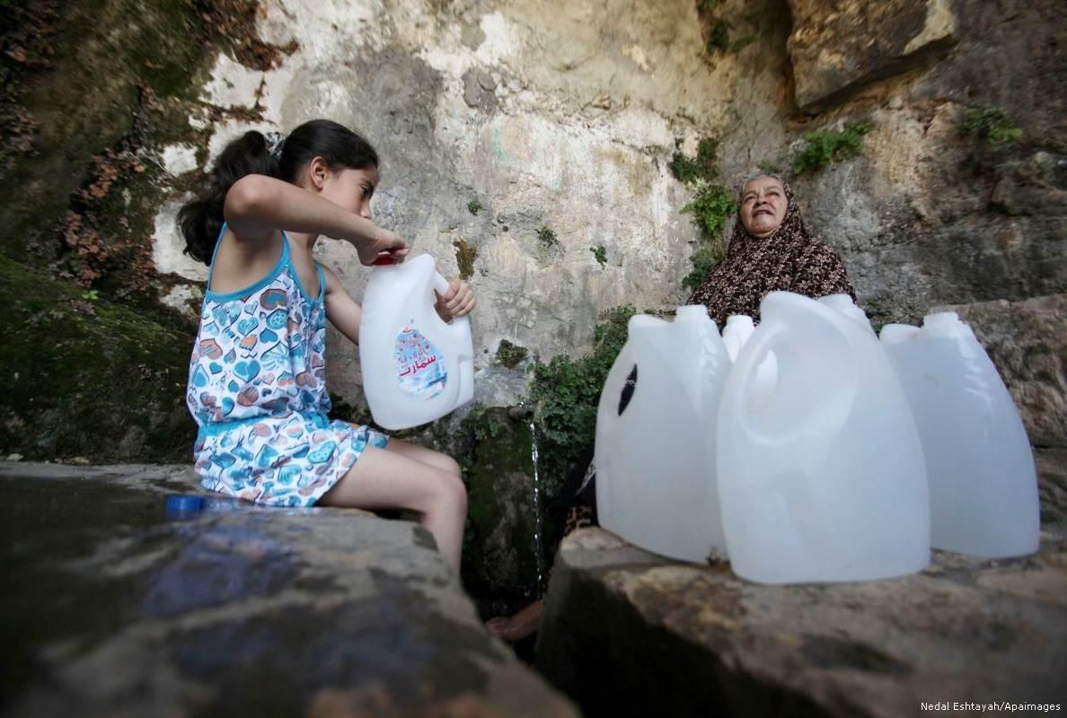 فتاة فلسطينية تملأ عبوات المياه من نبع في الضفة الغربية.