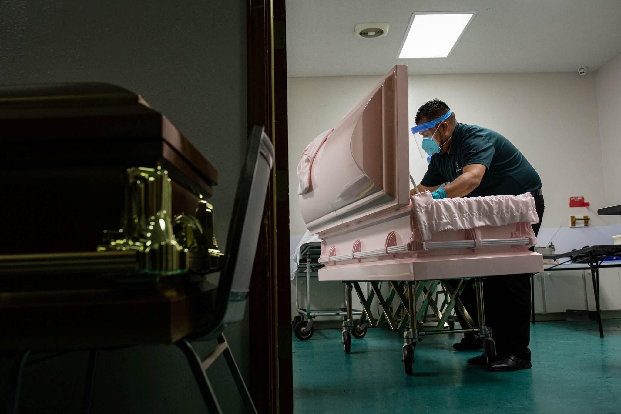 عامل يقوم بإعداد النعش لمتوفي بفيروس كورونا في براونزفيل بولاية تكساس.