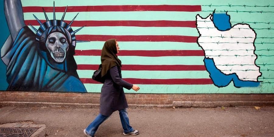 امرأة إيرانيّة تسير أمام لوحة جداريّة مناهضة للولايات المتحدة على السفارة الأميركية السابقة في طهران (رويرتز)