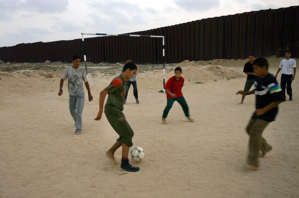 أطفالٌ فلسطينيون يلعبون الكرة على ملعب رمليّ في رفح (أ ف ب)