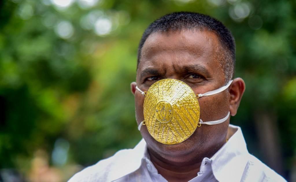 رجل أعمال هندي يرتدي قناع وجه مصنوع من الذهب للوقاية من تفشي فيروس كورونا (أ ف ب).