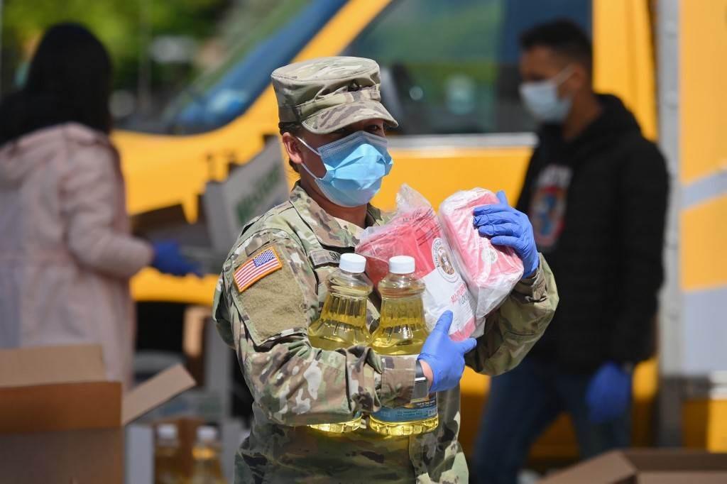 جندية من الحرس الوطني بالجيش الأميركي توزع الطعام في حي بروكلين بمدينة نيويورك (أ ف ب).