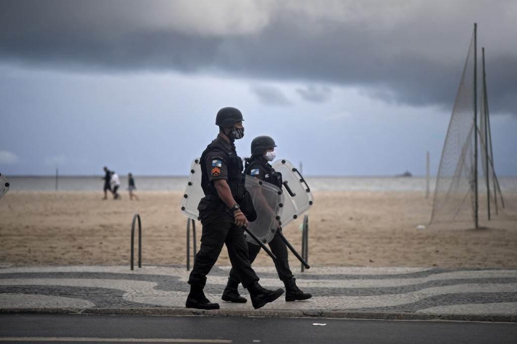 جنود الشرطة خلال احتجاج على الطريقة تتعامل بها الحكومة البرازيلية مع انتشار فيروس كورونا (أ ف ب).