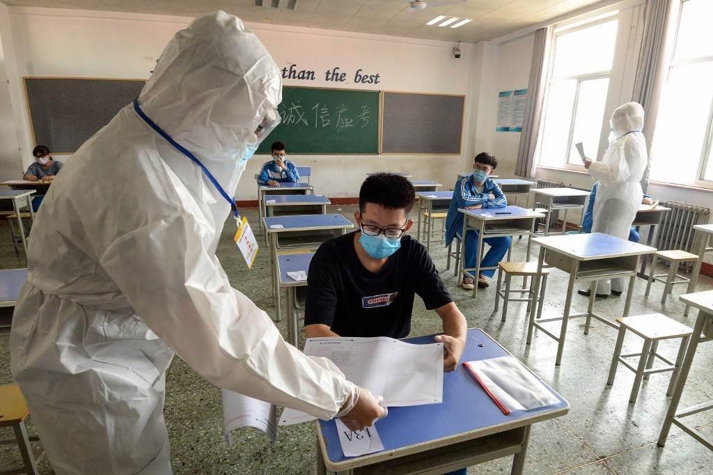 موظف يقوم بتوزيع الأوراق على الطلاب أثناء إجرائهم امتحان الدخول للجامعة الوطنية (أ ف ب)