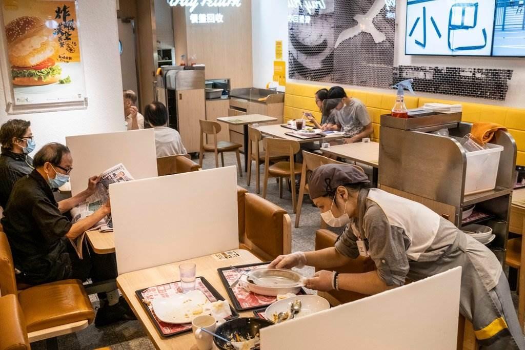 الزبائن في أحد مطاعم هونغ كونغ حيث يتم فصل الطاولات بألواح لمنع الإصابة بالفيروس.