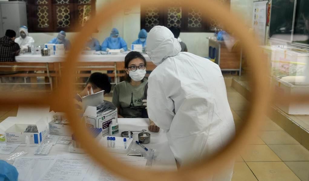 عمال في القطاع الصحي يجمعون عينات من اختبارات فيروس كورونا (أ ف ب)