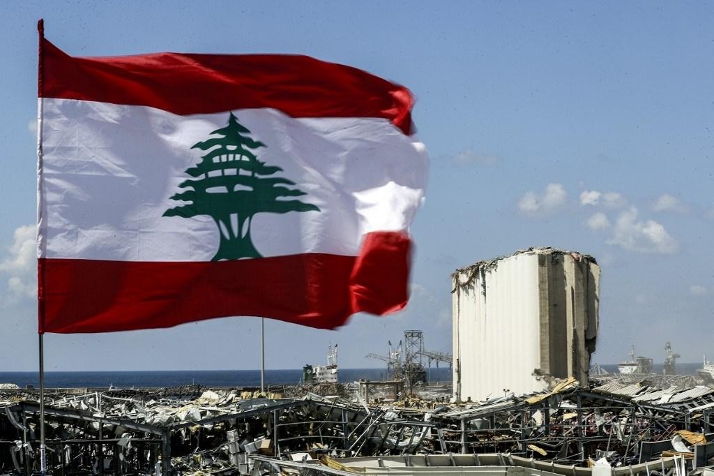 العلم اللبناني مرفوعاً قرب دمار مرفأ بيروت (أ.ف.ب)