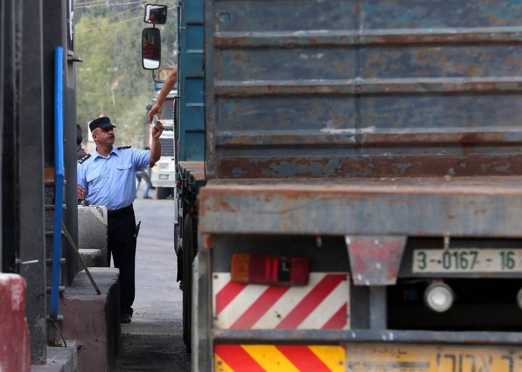 شرطي فلسطيني يتحقق من وثائق سائق عند بوابة معبر كرم أبو سالم (أ ف ب).