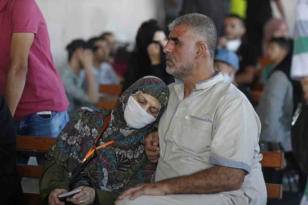 فلسطينيون ينتظرون العبور إلى الجانب المصري من معبر رفح الحدودي بعد فتحه اليوم استثنائياً (أ.ف.ب)