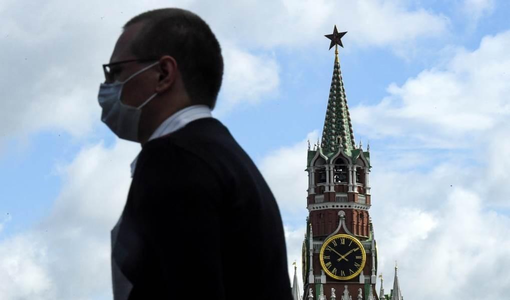 رجل يرتدي قناعاً للوجه يمشي أمام برج سباسكايا في الكرملين في الميدان الأحمر بوسط مدينة موسكو (أ ف ب)