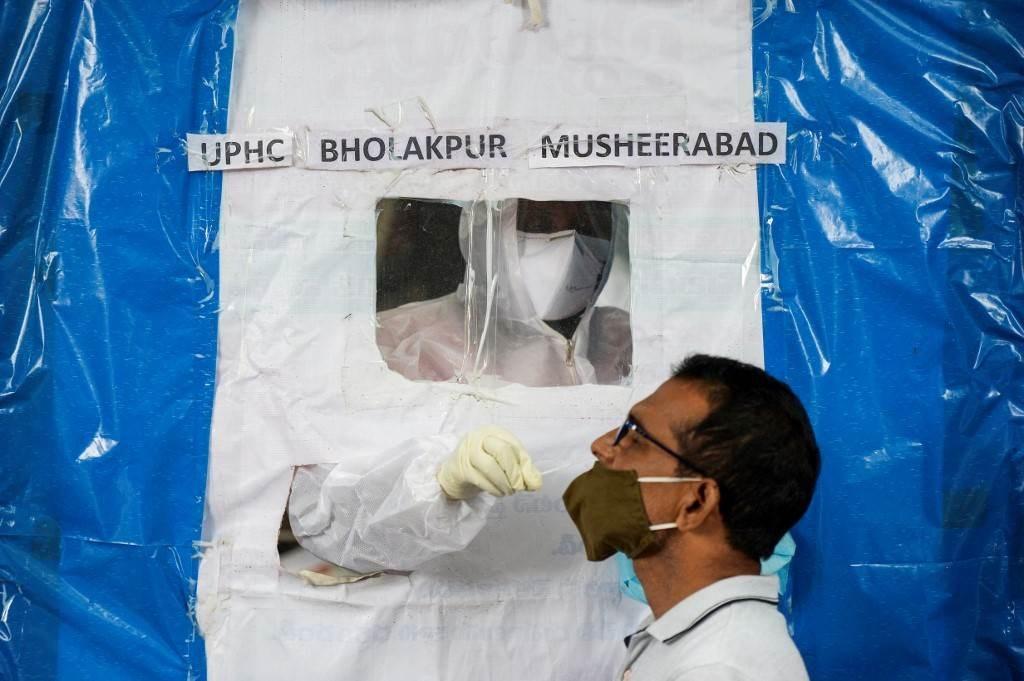 ممرض يجرب فحص لأحد السكان في حيدر أباد (أ ف ب).