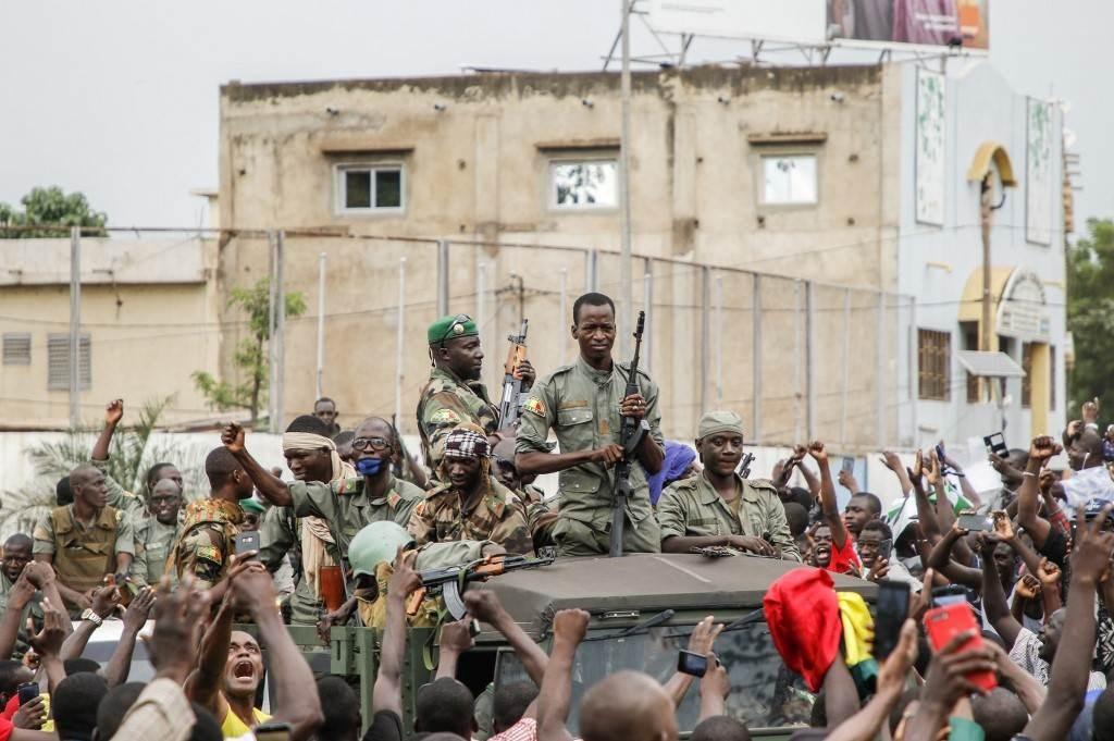 احتفل السكان بالقوات المسلحة المالية أثناء استعراضهم العسكري في ساحة الاستقلال في باماكو بعد الإطاحة بالرئيس المالي (أ ف ب)