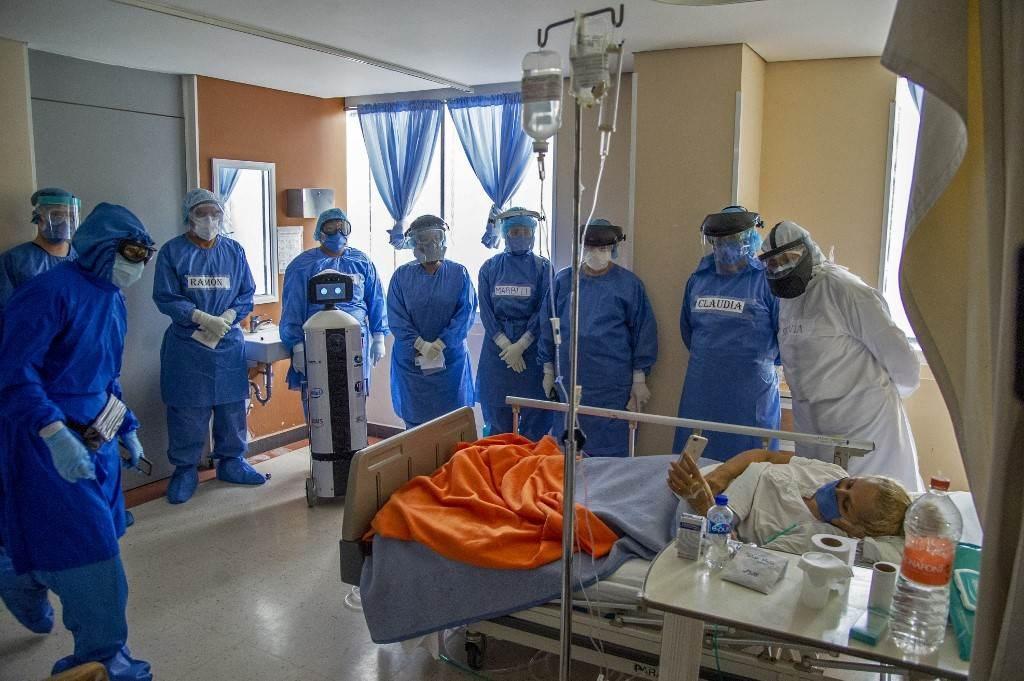 مصابة بفيروس كورونا يقف إلى جانبها أطباء وروبوت في مكسيكو (أ ف ب).