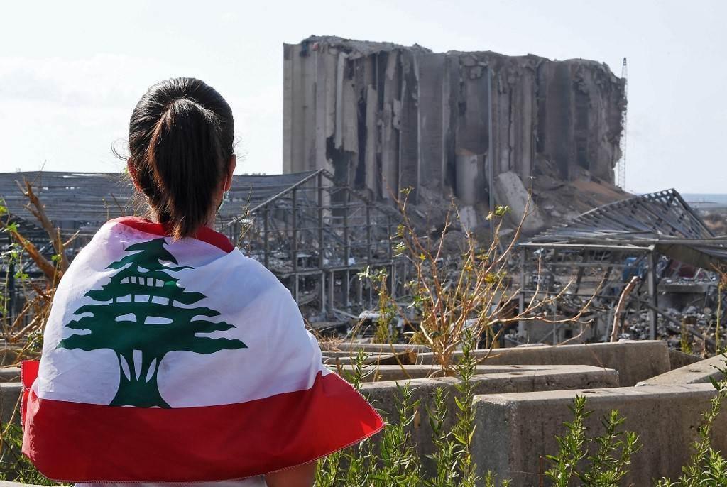 شابة لبنانيّة تقف أمام دمار مرفأ بيروت بعد الانفجار (أ.ف.ب)