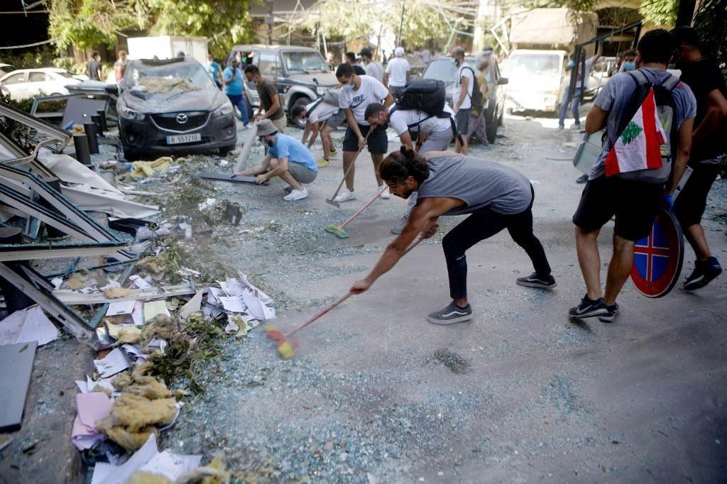 ناشطون لبنانيون يشاركون في حملة لتنظيف حي الجميزة المتضرر في بيروت (أ ف ب).