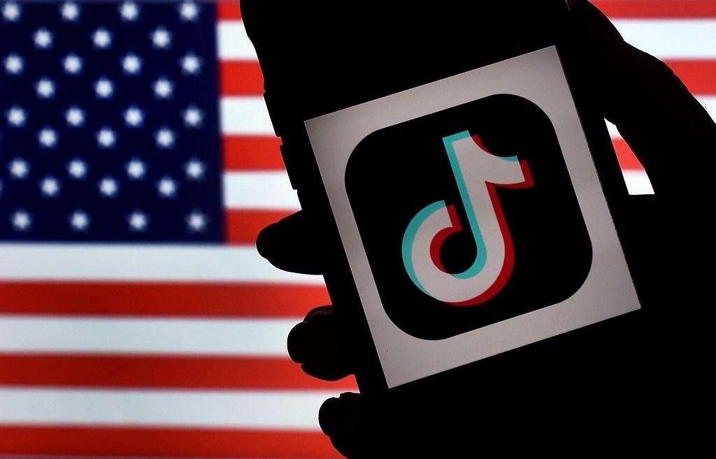 شعار TikTok على شاشة iPhone وفي الخلفية العلم الأميركي في فيرجينيا (أ.ف.ب)
