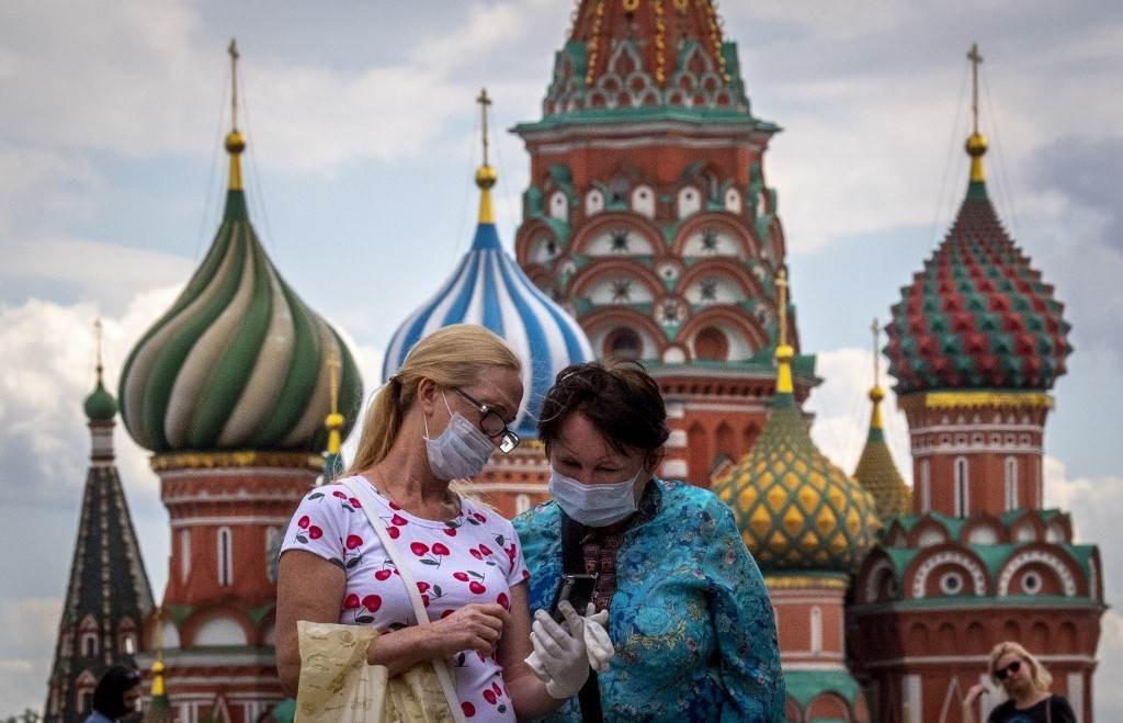 امرأتان ترتديان أقنعة للحماية من فيروس كورونا وسط مدينة موسكو (أ ف ب).