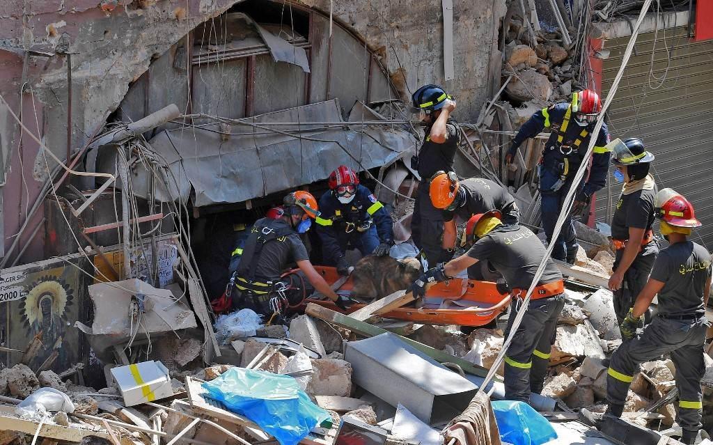 عناصر من الدفاع المدني اللبناني يبحثون تحت الأنقاض عن ناجين من انفجار بيروت (أ ف ب ).