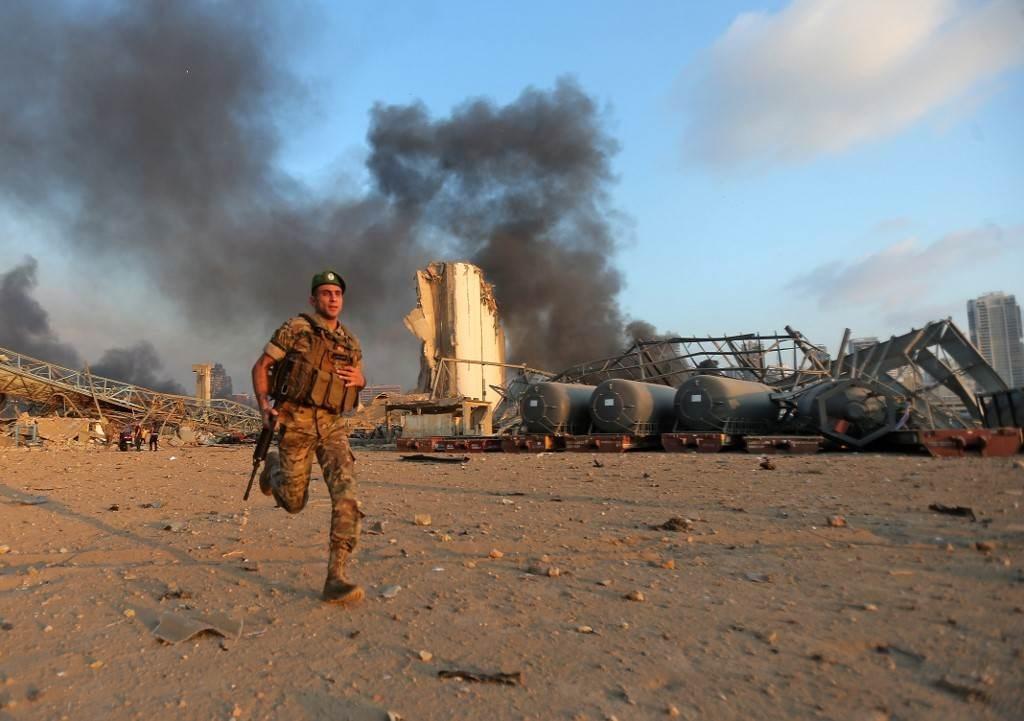 جندي من الجيش اللبناني يساعد في عمليات الإنقاذ في مرفأ بيروت (أ ف ب).