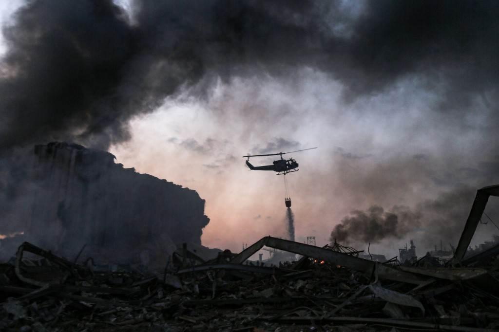 مروحية تحاول إطفاء الحريق الذي اشتعل جرّاء الإنفجار في مرفأ بيروت (أ ف ب).