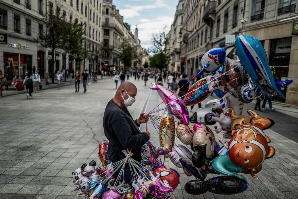 بائع متجول يرتدي قناع وجه يقف في وسط ليون (أ ف ب).