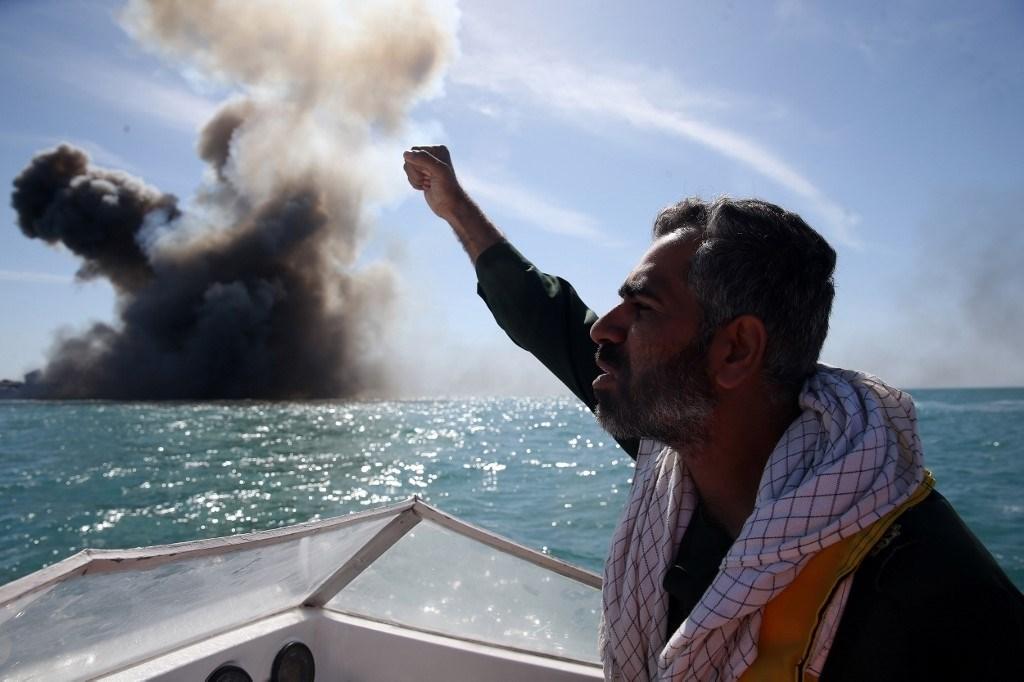 جندي في حرس الثورة الإيراني يردد شعارات بعد مهاجمة سفينة بحرية خلال مناورة عسكرية في مضيق هرمز عام 2015 (أ.ف.ب)