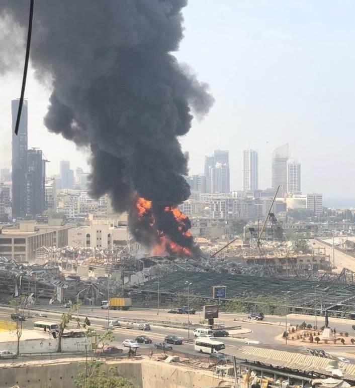 حريق مرفأ بيروت اليوم فيما يظهر دمار انفجار 3 آب/أغسطس 2020 في الصورة