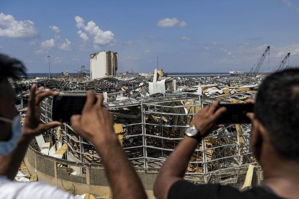 مواطنون مقابل مرفأ بيروت الذي وقع فيه انفجار ضخم في 4 آب الماضي (أ ف ب).