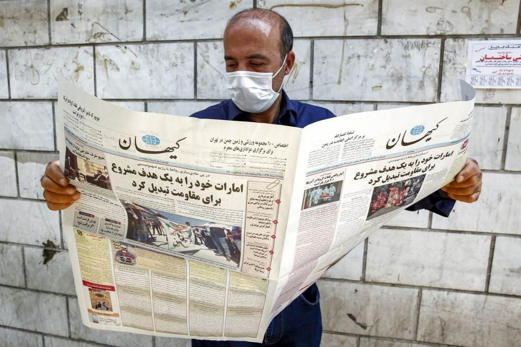 رجل يقرأ صحيفة كيهان الإيرانية مع عنوان رئيسي في صفحتها الأولى عن التطبيع الإماراتي (أ ف ب).