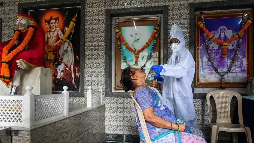 عامل صحة يأخذ عينة من سيدة لإجراء فحص كوفيد-19 في معبد في بومباي، في 15 أيلول/سبتمبر 2020 اندرانيل مخرجي (ا ف ب)