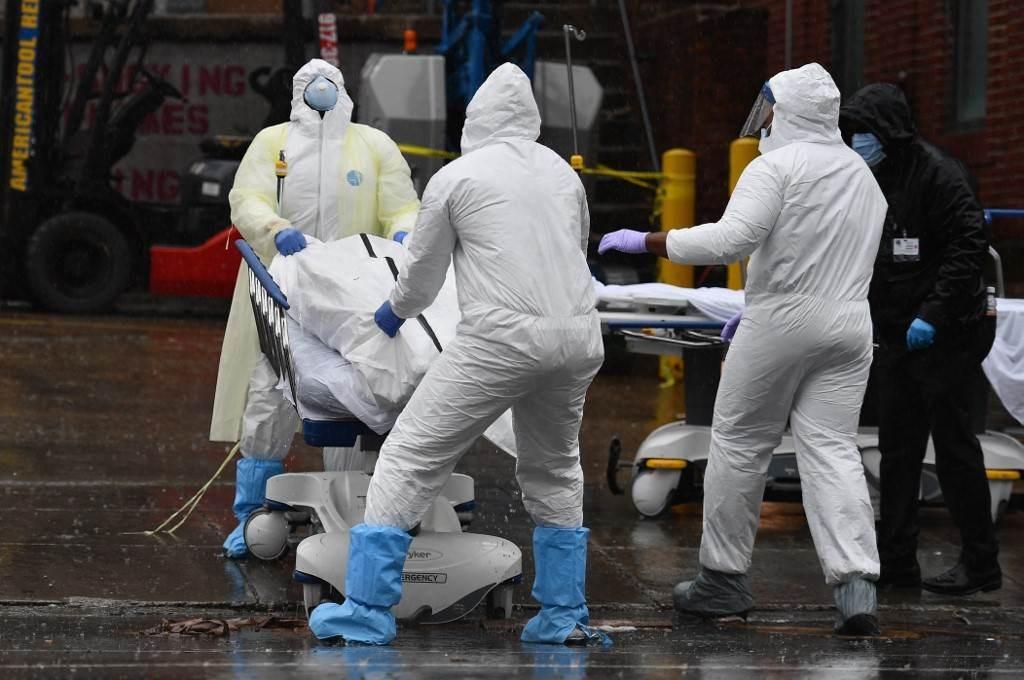 نقل مريض متوفى بفيروس كورونا إلى شاحنة مبردة في مركز مستشفى بروكلين (أ ف ب).