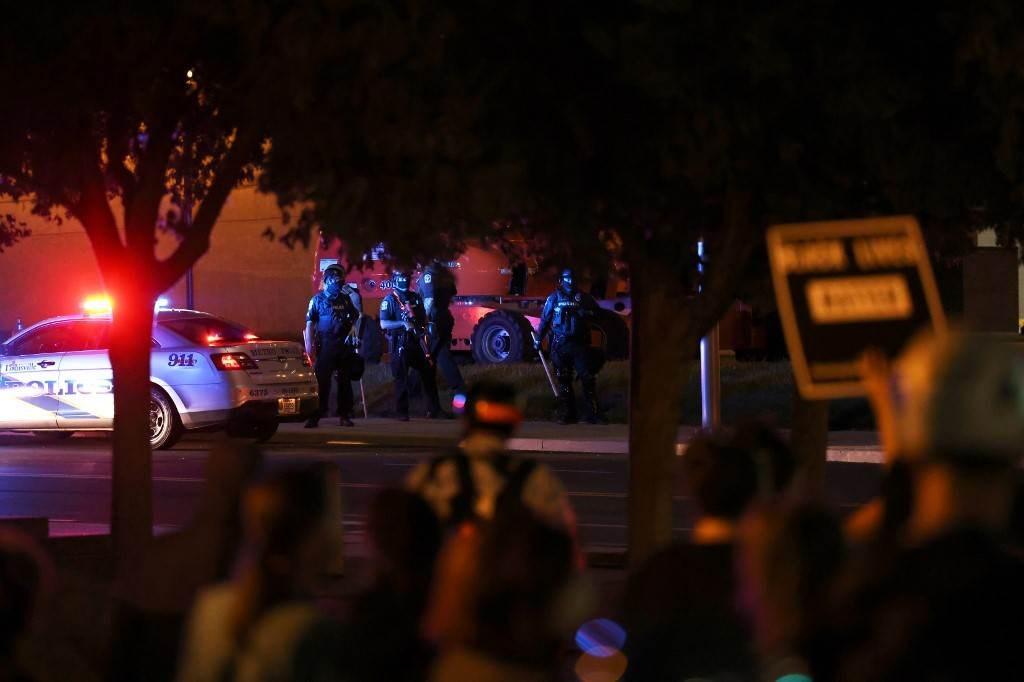 ضباط شرطة لويزفيل ينظرون إلى المتظاهرين في لويزفيل - ولاية كنتاكي (أ ف ب).