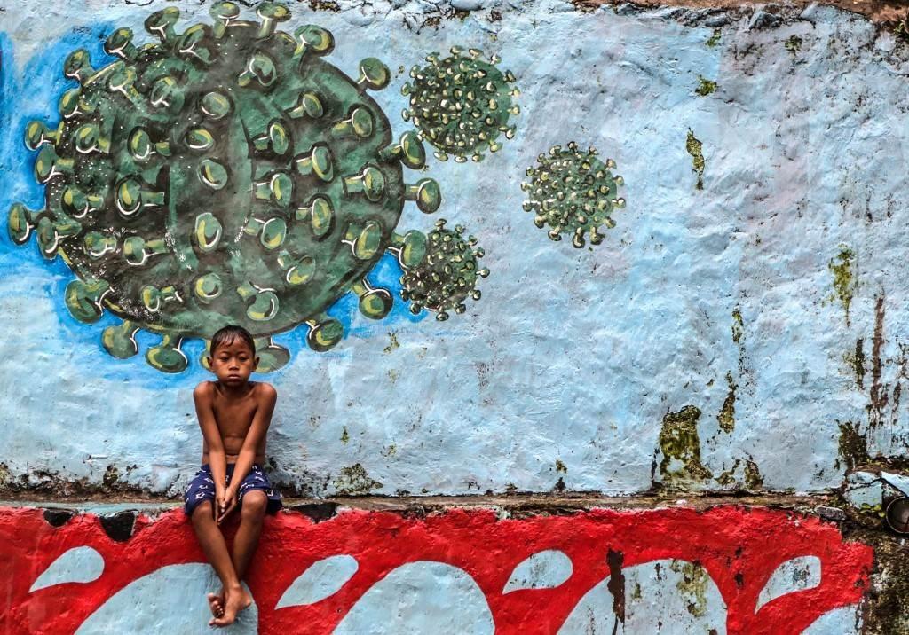 طفل يجلس أمام لوحة جدارية تمثل فيروس في بوجور (أ ف ب).