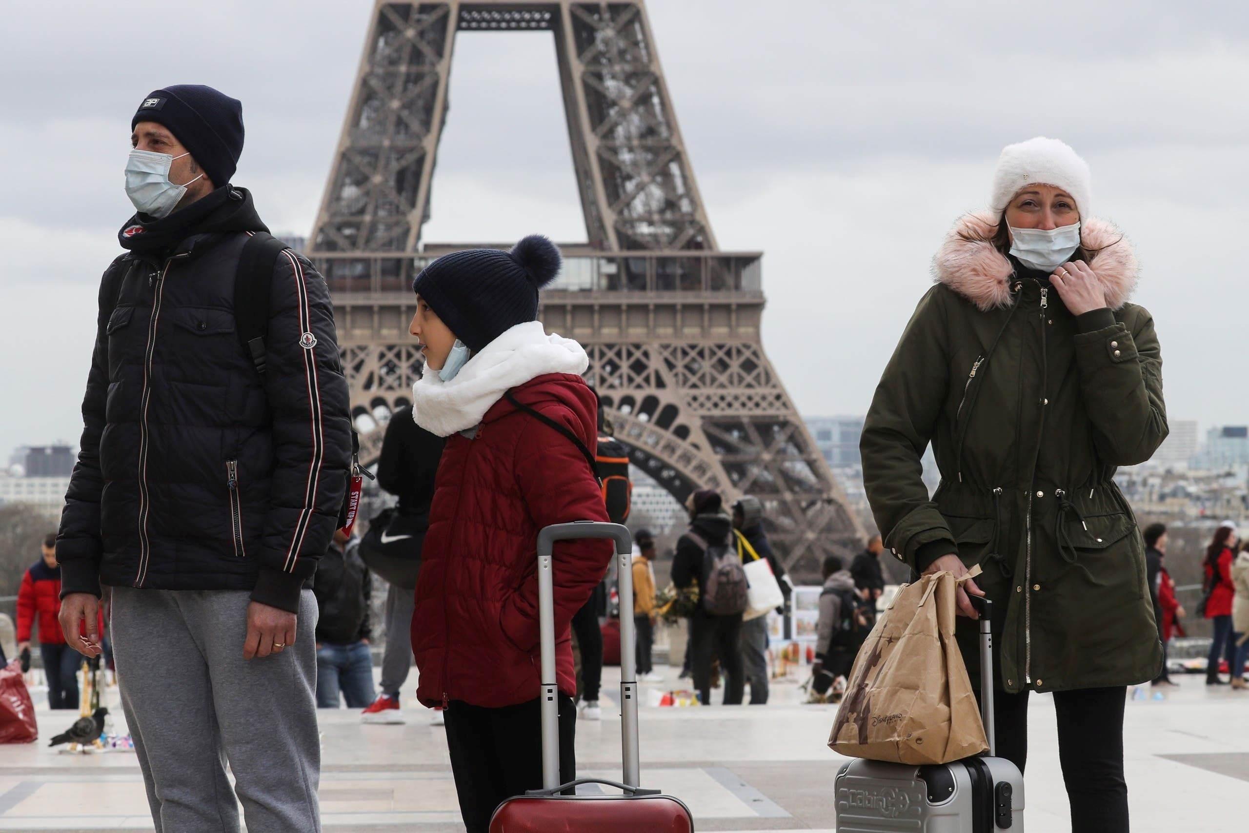 أشخاص يسيرون بالقرب من برج إيفل مرتدين أقنعة وسط تفشي فيروس كورونا (أ ف ب).