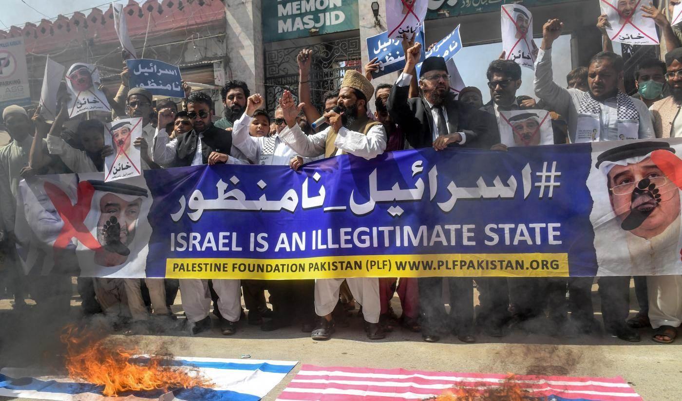 حرق العلمين الإسرائيلي والأميركي خلال تظاهرة مناهضة للتطبيع في مدينة كراتشي الباكستانية (أ ف ب)