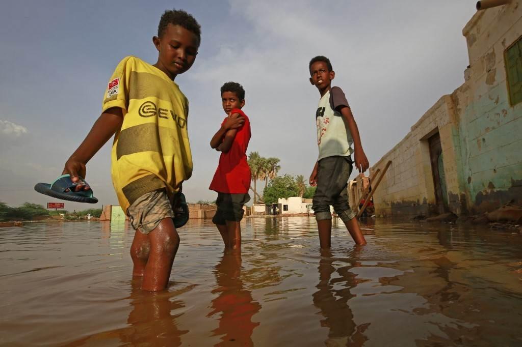 أطفال يشقون طريقهم عبر شارع غمرته المياه في السودان (أ ف ب).