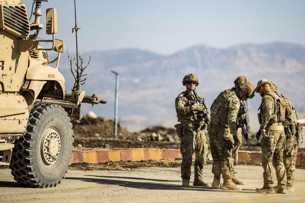 جنود أميركيون أمام آلية عسكرية قرب مدينة المالكية شمال شرق الحسكة (أ ف ب).