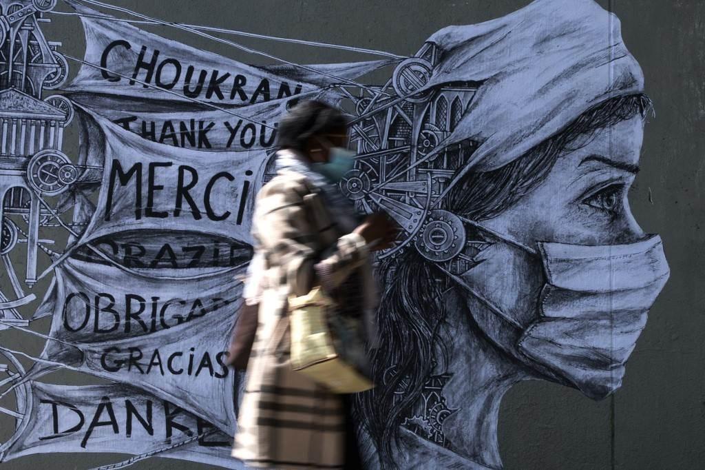 امرأة ترتدي قناعاً واقياً تمرّ بجانب غرافيتي شكر لمقدمي الرعاية الصحيّة في فرنسا خلال جائحة كورونا (أ.ف.ب)