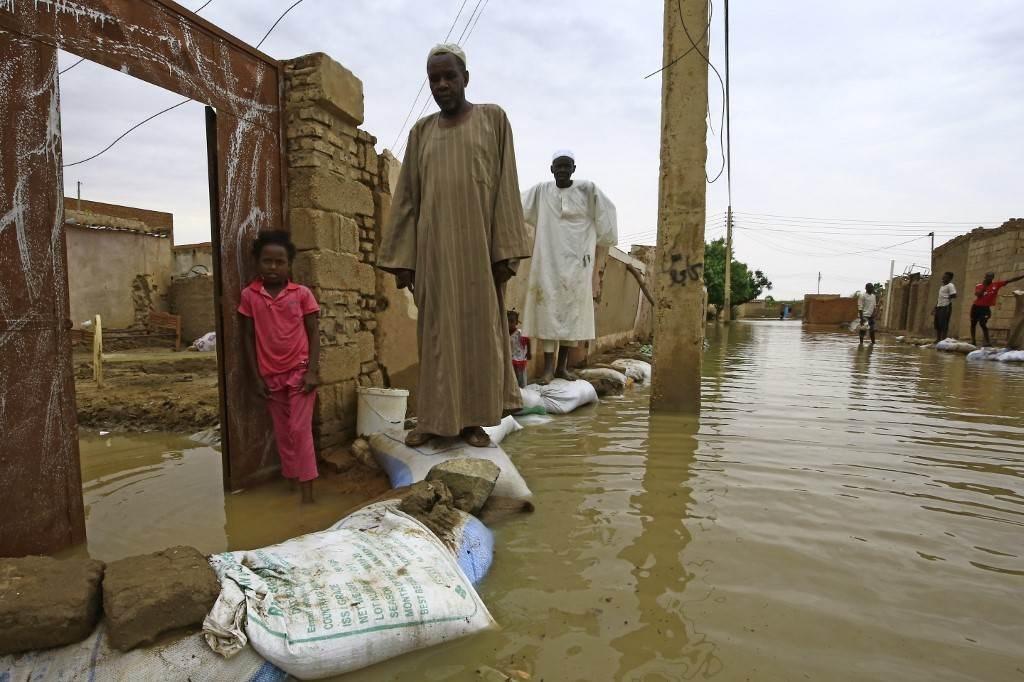 سودانيون يمشون على أكياس رمل للوصول إلى منازلهم على طول شارع غمرته المياه في العاصمة الخرطوم (أ.ف.ب)