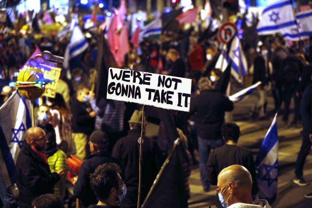 إسرائيليون يرفعون لافتات وأعلام أثناء مشاركتهم في مظاهرة ضد نتنياهو بالقرب من المقر الرسمي له في القدس 9 كانون الثاني/يناير 2021 (أ ف ب)