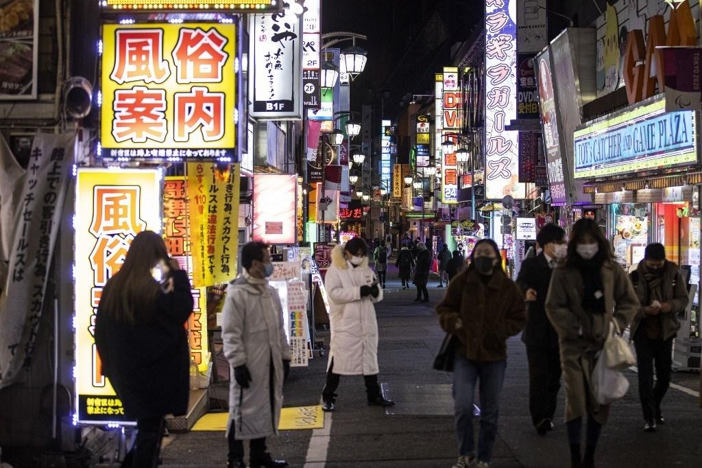 أشخاص يسيرون في أحد شوارع توكيو مرتدين الكمامة (أ ف ب - أرشيف)