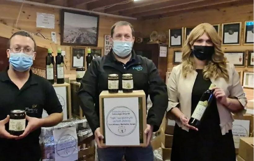 رئيس مجلس السامرة الإقليمي يحمل صندوقاً من مصنع نبيذ ترورو في فلسطين المحتلة.
