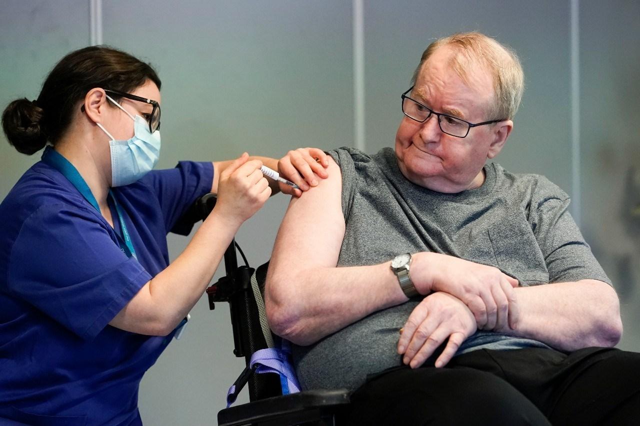رجل مسن يتلقى اللقاح ضد فيروس كورونا في النرويج